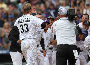 Photo - Colorado Rockies' Justin Morneau, left, is mobbed by teammates at home plate after Morneu hit a two-run, walkoff home run against the San Diego Padres in the 10th inning of the Rockies' 8-6 victory in 10 innings of a baseball game in Denver on Sunday, May 18, 2014. (AP Photo/David Zalubowski)