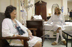 Photo - In this Jan. 14, 2014 photo, Irma Myers-Santana, left, and her sister Anna Williamson visit in Williamson's hospital room in Houston. Earlier this month the sisters ended up in the same operating room, each getting one lung from the same donor. (AP Photo/Pat Sullivan)