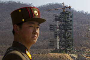 Photo -   A North Korean soldier stands in front of the country's Unha-3 rocket, slated for liftoff between April 12-16, at a launching site in Tongchang-ri, North Korea on Sunday April 8, 2012. North Korean space officials have moved a long-range rocket into position for this week's controversial satellite launch, vowing Sunday to push ahead with their plans in defiance of international warnings against violating a ban on missile activity.(AP Photo/David Guttenfelder)