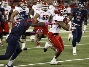 Photo - Utah's Lucky Radley (44) out runs the reach of Arizona's Jonathan McKnight (6) for a long gain in the first half of an NCAA college football game, Saturday, Oct. 19, 2013, in Tucson, Ariz.  (AP Photo/Wily Low)