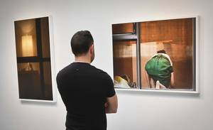 Photo - A visitor views the photography of Arne Svenson on Thursday, May 16, 2013 at the Julie Saul Gallery in New York.  Residents of a New York luxury apartment building are upset over the exhibition by Svenson who  secretly made their pictures from his window across the street. (AP Photo/Bebeto Matthews)