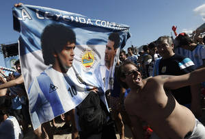 Photo - A soccer fan of Argentina poses with a banner of Maradona and Lionel Messi before the start of the final World Cup match between Argentina and Germany, on Copacabana beach in Rio de Janeiro, Brazil, Sunday, July 13, 2014.  (AP Photo/Silvia Izquierdo)