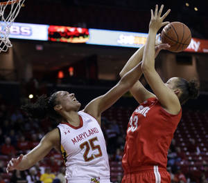 Photo - Maryland forward Alyssa Thomas, left, blocks a shot attempt by Ohio State center Ashley Adams in the first half of an NCAA college basketball game in College Park, Md., Wednesday, Dec. 4, 2013. (AP Photo/Patrick Semansky)