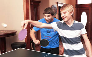 Photo - J.R. Kalmeyer, right, and his friend, Cole Daniel, both 14, play table tennis with friends in Kalmeyer's home in far west Oklahoma City, Tuesday afternoon, July 17, 2012. Photo by Jim Beckel, The Oklahoman.