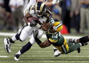 Photo -   St. Louis Rams running back Daryl Richardson, left, runs with the ball as Green Bay Packers strong safety Charles Woodson defends during the first quarter of an NFL football game Sunday, Oct. 21, 2012, in St. Louis. (AP Photo/Tom Gannam)