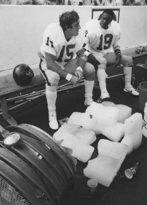 "Photo - FOOTBALL OU UNIVERSITY OF OKLAHOMA 1982 51: Caption reads ""West Virginia quarterback Jeff Hostetler and flanker Wayne Brown get some relief from the heat as a fan blows cool air off several bags of ice."" Photo taken by Jim Argo. Date photo was taken unknown. Photo was published in The Daily Oklahoman 9-12-1982."