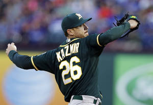 Photo - Oakland Athletics starting pitcher Scott Kazmir delivers to the Texas Rangers in the first inning of a baseball game, Tuesday, April 29, 2014, in Arlington, Texas. (AP Photo/Tony Gutierrez)