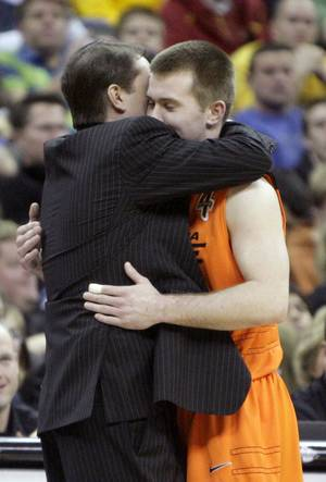 photo - Oklahoma State head coach Travis Ford hugs Oklahoma's Keiton Page (12) in the final seconds of the Big 12 tournament men's basketball game between the Oklahoma State Cowboys and Missouri Tigers the Sprint Center, Thursday, March 8, 2012. Photo by Sarah Phipps, The Oklahoman