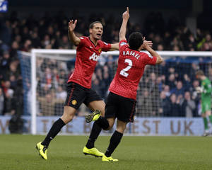 Photo - Manchester United's Rafael de Silva, right, celebrates after scoring against Queens Park Rangers during their English Premier League soccer match at Loftus Road ground in London, Saturday, Feb. 23, 2013. (AP Photo/Lefteris Pitarakis)