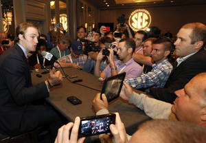 Photo - Mississippi quarterback Bo Wallace, left, speaks to the media at the Southeastern Conference NCAA college football media days, Thursday, July 17, 2014, in Hoover, Ala. (AP Photo/Butch Dill)