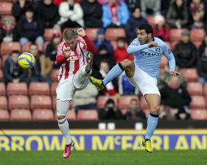 photo - Stoke City's Michael Kightly, left, and Manchester City's Carlos Tevez battle for the ball during their English FA Cup fourth round soccer match at the Britannia Stadium in Stoke on Trent, England, Saturday Jan. 26, 2013. (AP Photo/Clint Hughes)