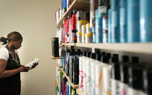 photo - Krystal Skeete organizes products at Supercuts at 23V Retail Plaza, 2519 NW 23, a redevelopment project by Baker First Commercial Real Estate Services, which is celebrating its 25th year. Supercuts is having its grand opening today. PHOTOS BY SARAH PHIPPS, The Oklahoman