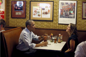 Photo - President Barack Obama talks with Rebekah Erler, of Minneapolis at Matts Bar before going to a town hall meeting at Minnehaha Park, Thursday, June 26, 2014, in Minneapolis. The president is in Minneapolis for the first in a series of Day-in-the-Life visits he plans to make across the country this summer. (AP Photo/The Star Tribune, Jerry Holt, Pool)
