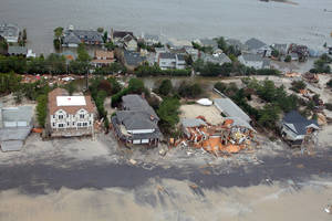 Photo - FILE - This Oct. 30, 2012 file photo provided by the U.S.Air Force shows an aerial view of  damage to the New Jersey shoreline following Superstorm Sandy. There are a rising number of homes damaged by Sandy hitting the market -  ranging from 10 percent off pre-storm prices for upscale homes in New York's Long Island and the Jersey Shore to up to 60 percent off modest bungalows in Staten Island and Queens - but it's very much a game of buyer beware.  (AP Photo/U.S. Air Force, Master Sgt. Mark C. Olsen, File)