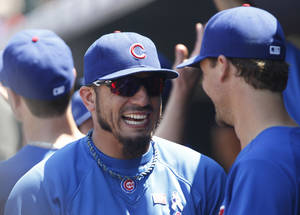 Photo - Chicago Cubs pitcher Matt Garza, left, jokes with outfielder Cole Gillespie before facing the Colorado Rockies in a baseball game in Denver, Sunday, July 21, 2013. (AP Photo/David Zalubowski)