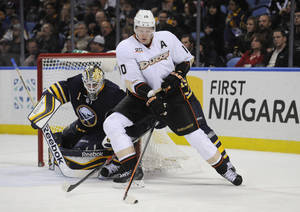 Photo - Anaheim Ducks right winger Corey Perry (10) moves the puck in front of Buffalo Sabres goaltender Jhonas Enroth (1), of Sweden, during the second period of an NHL hockey game in Buffalo, N.Y., Saturday, Nov. 2, 2013. (AP Photo/Gary Wiepert)