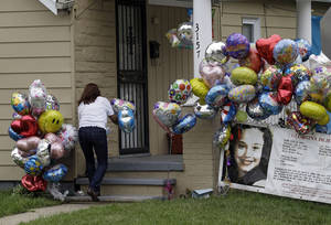Photo - Culema Nevarez adds balloons to a growing tribute outside the home of Gina DeJesus in Cleveland, Friday, May 10, 2013. DeJesus was freed Monday from the home of Ariel Castro where she and two other women had been held captive for nearly a decade.  (AP Photo/Mark Duncan)