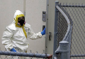 Photo - A Prince George's County, Md. firefighter dressed in a protective suit walks into a government mail screening facility in Hyattsville, Md., Wednesday, April 17, 2013. Police swept across the U.S. Capitol complex to chase a flurry of reports of suspicious packages and envelopes Wednesday after preliminary tests indicated poisonous ricin in two letters sent to President Barack Obama and a Mississippi senator.  (AP Photo/Alex Brandon)