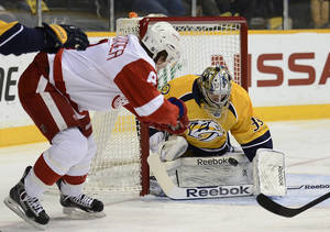 Photo - Detroit Red Wings left wing Justin Abdelkader, left, flips the puck past Nashville Predators goalie Marek Mazanec (39), of the Czech Republic, for a goal in the first period of an NHL hockey game on Monday, Dec. 30, 2013, in Nashville, Tenn. (AP Photo/Mark Zaleski)