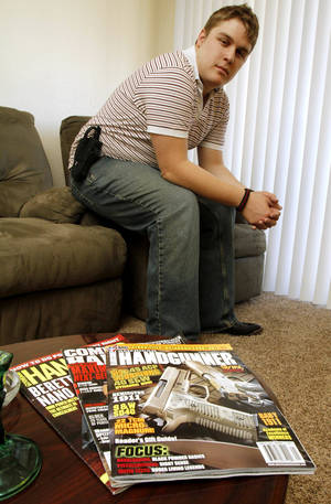Photo - Scott  Hannaford sits last week  with his  holster  and gun magazines in Tulsa.  Photo by  JAMES GIBBARD,  Tulsa World