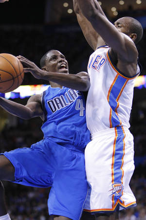 Photo - Dallas Mavericks guard Darren Collison, left, goes to the basket in front of Oklahoma City Thunder forward Serge Ibaka, right, during the first quarter of an NBA basketball game in Oklahoma City, Thursday, Dec. 27, 2012. (AP Photo/Alonzo Adams)