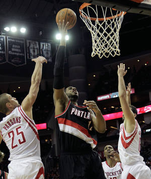 Photo - Portland Trail Blazers forward LaMarcus Aldridge (12) drives to the basket past  Houston Rockets forward Chandler Parsons (25) during the first half of an NBA basketball game, Monday, Jan. 20, 2014, in Houston. (AP Photo/Bob Levey)