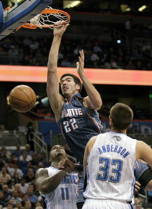 Photo -   Charlotte Bobcats' Byron Mullens (22) dunks the ball as he gets between Orlando Magic's Glen Davis (11) and Ryan Anderson (33) during the first half of an NBA basketball game, Wednesday, April 25, 2012, in Orlando, Fla. (AP Photo/John Raoux)