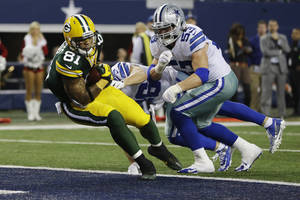 Photo - Green Bay Packers tight end Andrew Quarless (81) scores a touchdown as Dallas Cowboys outside linebacker Cameron Lawrence (53) and Sterling Moore (26) defends during the second half of an NFL football game, Sunday, Dec. 15, 2013, in Arlington, Texas. (AP Photo/Tony Gutierrez)
