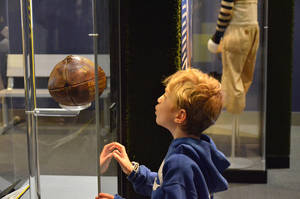 """Photo - This undated image provided by Liberty Science Center shows a young visitor at the museum looking at an artifact from an exhibit called """"Gridiron Glory."""" The Liberty Science Center is one of a number of places for Super Bowl fans to visit in New Jersey while in town for the championship game. (AP Photo/Liberty Science Center) (AP Photo/Liberty Science Center)"""