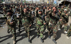 "Photo - Volunteers of the newly formed ""Peace Brigades"" participate in a parade in the Shiite stronghold of Sadr City, Baghdad, Iraq, Saturday, June 21, 2014. The armed group was formed after radical Shiite cleric Muqtatda al-Sadr called to form brigades to protect Shiite holy shrines against possible attacks by Sunni militants. (AP Photo/Khalid Mohammed)"