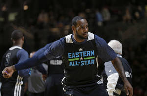 Photo - East Team's LeBron James, of the Miami Heat, throws a pair of Mardi Gras beads to the crowd during NBA All-Star game basketball practice in New Orleans, Saturday, Feb. 15, 2014. (AP Photo/Gerald Herbert)