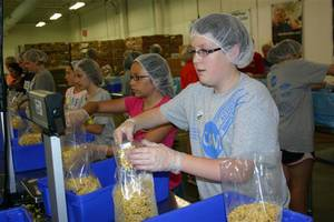 Photo - Julie Bennett, 12, fills bags with corn in an assembly line at the Central Oklahoma Regional Food Bank in July as part of a summer mission camp.