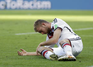 Photo - Germany's Christoph Kramer lies on the pitch after getting hit in the face by Argentina's Ezequiel Garay's shoulder during the World Cup final soccer match between Germany and Argentina at the Maracana Stadium in Rio de Janeiro, Brazil, Sunday, July 13, 2014. (AP Photo/Natacha Pisarenko)