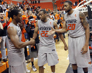 Photo - From left, OSU's Brian Williams (4), Markel Brown (22) and Michael Cobbins (20) stop to shake hands with each other before leaving the floor after the Bedlam men's college basketball game between the Oklahoma State University Cowboys and the University of Oklahoma Sooners at Gallagher-Iba Arena in Stillwater, Okla., Monday, Jan. 9, 2012. OSU beat OU, 72-65. Photo by Nate Billings, The Oklahoman