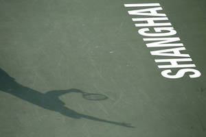 Photo - The shadow of Jo-Wilfried Tsonga of France is cast on the court as he serves to Pablo Andujar of Spain during their singles match at the Shanghai Masters tennis tournament at Qizhong Forest Sports City Tennis Center, in Shanghai, China, Wednesday, Oct. 9, 2013. (AP Photo/Eugene Hoshiko)