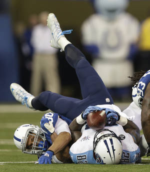 Photo - Tennessee Titans' Delanie Walker (82) makes a catch while being tackled by Indianapolis Colts' LaRon Landry (30) during the first half of an NFL football game on Sunday, Dec. 1, 2013, in Indianapolis. (AP Photo/Michael Conroy)