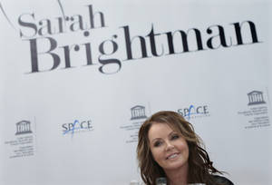 Photo -   British singer Sarah Brightman smiles during news conference in Moscow, Russia, Wednesday, Oct. 10, 2012. Brightman is to become the first-ever global recording artist to take a spaceflight, teaming up with Space Adventures for a journey to the International Space Station (ISS). (AP Photo/Mikhail Metzel)