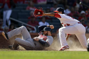 Photo - Atlanta Braves' Ryan Doumit, left, scores on a wild pitch by St. Louis Cardinals relief pitcher Carlos Martinez, right, as Martinez covers home during the ninth inning of a baseball game Sunday, May 18, 2014, in St. Louis. (AP Photo/Jeff Roberson)