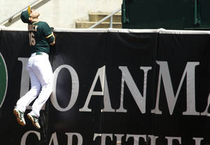 Oakland Athletics' Josh Reddick climbs the wall chasing after Houston Astros' Marwin Gonzalez's solo homer in the fourth inning of a baseball gmae in Oakland, Calif. on Sunday, April 20, 2014. (AP Photo/Matthew Sumner)