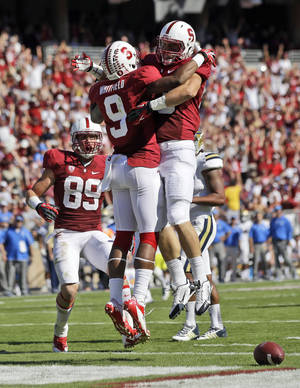 Photo - Stanford wide receiver Kodi Whitfield (9) celebrates his touchdown catch with teammate Davis Dudchock, right, during the second half of an NCAA college football game against UCLA  on Saturday, Oct. 19, 2013, in Stanford, Calif. Stanford won 24-10. (AP Photo/Marcio Jose Sanchez)