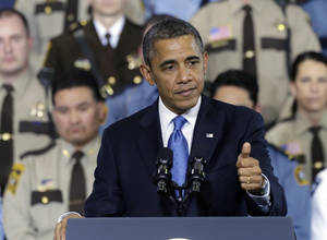 photo - President Barack Obama gestures as he speaks about his gun violence proposals, Monday, Feb. 4, 2013, at the Minneapolis Police Department's Special Operations Center in Minneapolis, where he outlined his plan before law enforcement personnel.  (AP Photo/Jim Mone)