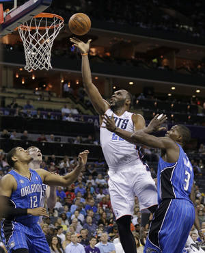 Photo - Charlotte Bobcats' Al Jefferson, center, shoots between Orlando Magic's Tobias Harris, left, and Dewayne Dedmon, right, during the first half of an NBA basketball game in Charlotte, N.C., Friday, April 4, 2014. (AP Photo/Chuck Burton)