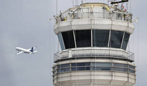Photo -   A passenger jet flies past the FAA control tower at Washington's Ronald Reagan National Airport.  AP File Photo  <strong>Cliff Owen -  AP </strong>