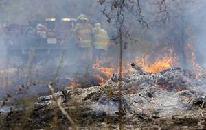 Photo -  In this Aug. 5 file photo, Mannford firefighters work to battle a wildfire just west of Mannford on West 31st Street MIKE SIMONS/Tulsa World File