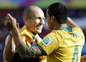 Photo - Netherlands' Arjen Robben, left, hugs Australia's Tim Cahill following the team's 3-2 loss to the Netherlands during the group B World Cup soccer match between Australia and the Netherlands at the Estadio Beira-Rio in Porto Alegre, Brazil, Wednesday, June 18, 2014.  (AP Photo/Fernando Vergara)