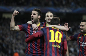 Photo - Barcelona's Lionel Messi, center, celebrates scoring the opening goal from a penalty with team mates Cesc Fabregas, left, and Andres Hiniesta during the Champions League first knock out round soccer match between Barcelona and Manchester City at the Etihad Stadium, Manchester, England, Tuesday Feb. 18, 2014. (AP Photo/Jon Super)
