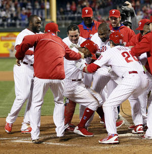 Photo - The Philadelphia Phillies surround Jimmy Rollins, center, who hit a solo home run in the bottom of the tenth inning to win a baseball game against the Miami Marlins, Saturday, April 12, 2014, in Philadelphia. The Phillies won 5-4. (AP Photo/Tom Mihalek)