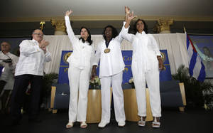 "Photo - In this Friday, May 20, 2013 photo, Cuban dissidents Ladies in White, from left, Laura Labrada Pollan, Berta Soler, and Belkis Cantillo acknowledge the guests at the Freedom Tower in Miami. MDC President Dr. Eduardo J. Padron, far left, presented Soler with MDC's Presidential Medal in homage to all the Ladies in White engraved, ""Guardians of Freedom."" Ladies in White is a group of women that began marching peacefully after the arrests of their sons and husbands in a 2003 crackdown on dissidents. They have faced detention and violence from pro-government mobs. (AP Photo/Alan Diaz)"