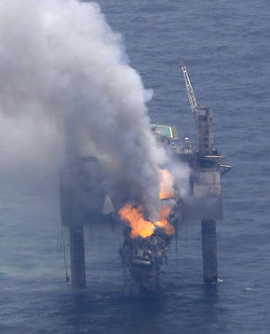 Photo - A fire is seen on the Hercules 265 drilling rig in the Gulf of Mexico off the coast of Louisiana, Wednesday, July 24, 2013. Natural gas spewed uncontrolled from the well on Tuesday after a blowout that forced the evacuation of 44 workers aboard the drilling rig, authorities said. No injuries were reported in the blowout. (AP Photo/Gerald Herbert)