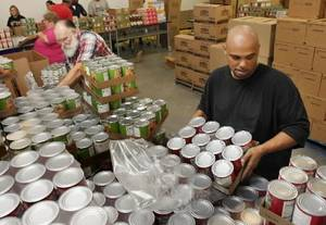 Photo - Food  Bank workers Roy Jarrett (left) and Ben Shannon load canned goods at the  Regional  Food   Bank of  Oklahoma in  Oklahoma City, OK, Thursday, Aug. 19, 2010. Photo by Paul Hellstern, The  Oklahoman